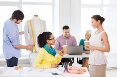 工作在办公室的微笑的时装设计师 免版税库存图片
