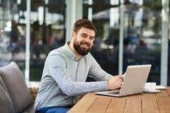 工作在办公室的微笑的有胡子的人 免版税库存图片