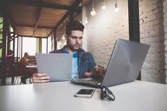 工作在办公室的新生意人,坐在服务台,查看膝上型计算机屏幕,微笑 免版税库存照片