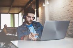 工作在办公室的新生意人,坐在服务台,查看膝上型计算机屏幕,微笑 库存照片