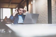 工作在办公室的新生意人,坐在服务台,查看膝上型计算机屏幕,微笑 免版税库存图片