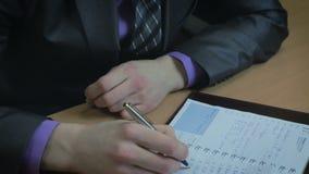 工作在办公室的生意人 他在日志写了 股票录像