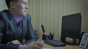 工作在办公室的生意人 他引起对心爱的他的画象的注意 股票录像