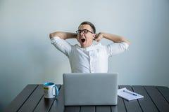 工作在办公室的疲乏的人 免版税库存图片