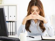 工作在办公室的疲乏的年轻女商人 库存图片