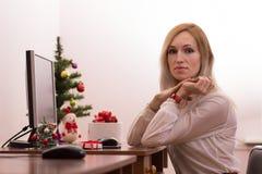 工作在办公室的白肤金发的妇女在圣诞节 免版税库存图片