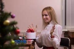 工作在办公室的笑的妇女在圣诞节 库存照片