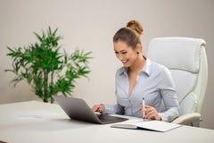工作在办公室的美丽的女商人 免版税图库摄影