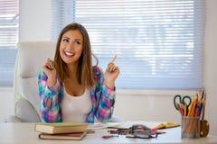 工作在办公室的美丽的少妇,当微笑时 图库摄影