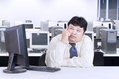 工作在办公室的肥胖商人 免版税图库摄影