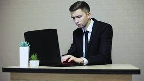 工作在办公室的英俊的商人,键入在膝上型计算机 股票视频