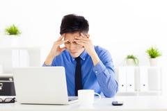 工作在办公室的被注重的商人 免版税库存图片