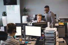 工作在办公室的被聚焦的年轻企业同事 免版税库存图片