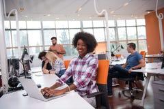 工作在办公室的非裔美国人的不拘形式的女商人 免版税库存照片