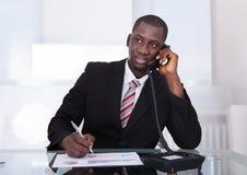 工作在办公室的非洲商人 免版税库存照片