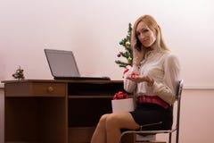 工作在办公室的高兴的妇女在圣诞节 免版税库存照片