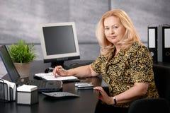 工作在办公室的高级妇女 免版税库存照片