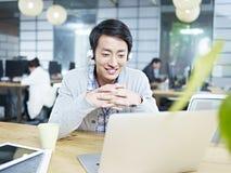 工作在办公室的年轻亚裔设计师 免版税图库摄影