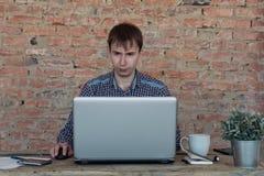 工作在办公室的年轻人,坐在书桌,看便携式计算机屏幕 免版税图库摄影