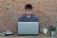 工作在办公室的年轻人,坐在书桌,看便携式计算机屏幕 免版税库存照片