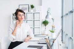 工作在办公室的年轻女实业家,键入,使用计算机 在网上搜寻信息的被集中的妇女 图库摄影