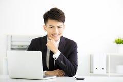 工作在办公室的年轻微笑的商人 库存图片