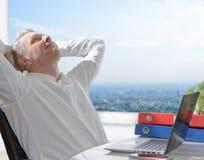 工作在办公室的满意的商人 免版税库存照片