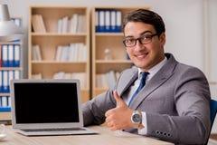 工作在办公室的年轻英俊的商人 免版税图库摄影