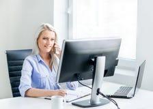 工作在办公室的年轻,可爱和确信的女商人 免版税库存照片