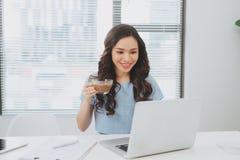 工作在办公室饮用的咖啡的亚裔妇女微笑对书桌 库存照片