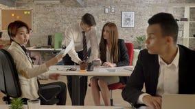 工作在办公室,亚裔妇女给黑人文件,白种人人民的混杂的种族的商人 股票录像