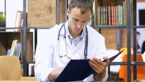 工作在办公室,医疗报告的愉快的年轻医生 图库摄影