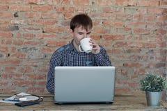 工作在办公室,坐在书桌,看便携式计算机屏幕和喝咖啡的年轻人 免版税库存照片