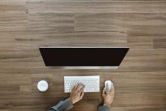 工作在办公桌和使用一台台式计算机的商人 库存图片
