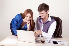 工作在办公桌的商人,妇女使用一台膝上型计算机,并且她的院长观看屏幕 免版税库存照片