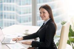 工作在办公桌的微笑的快乐的年轻女实业家与 库存照片