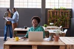 工作在办公桌的微笑的非洲女实业家 库存图片