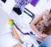 工作在办公桌的新可爱的女性时装设计师,画,当联系在移动电话时 库存图片