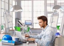 工作在办公桌的年轻建筑师 免版税库存照片