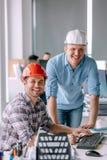 工作在办公楼的英俊的微笑的建筑师 免版税库存照片