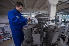 工作在包装的宽松食物机器的工作者 免版税图库摄影