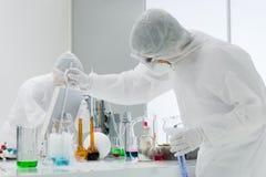 工作在化学实验室的人们 免版税库存照片