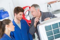 工作在压缩机单位的空调安装工 免版税库存照片