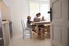 工作在厨房用桌上的妈咪和两个孩子,看见从门道入口 库存图片
