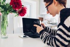 工作在厨房里的自由职业者摄影师 使用照相机,妇女研究膝上型计算机 家庭工作 库存图片