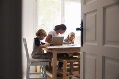 工作在厨房,关闭里的妈咪和两个孩子从门道入口 库存图片