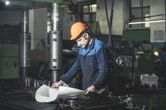 工作在反对机器背景的生产从的 免版税库存图片