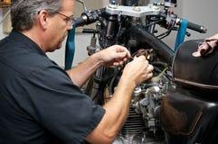 工作在古色古香的摩托车的技工 免版税库存照片