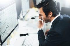 工作在台式计算机上的晴朗的办公室的商人,当坐在桌上时 被弄脏的背景,水平 免版税图库摄影