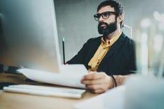 工作在台式计算机上的晴朗的办公室的年轻有胡子的人,当坐在木桌上时 商人佩带的眼睛 免版税图库摄影